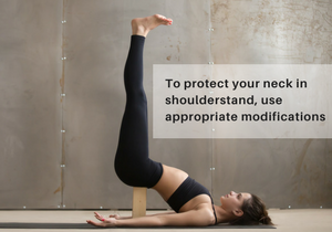A woman in Shoulderstand (Salamba Sarvangasana) using a block under her lower back to help protect the neck