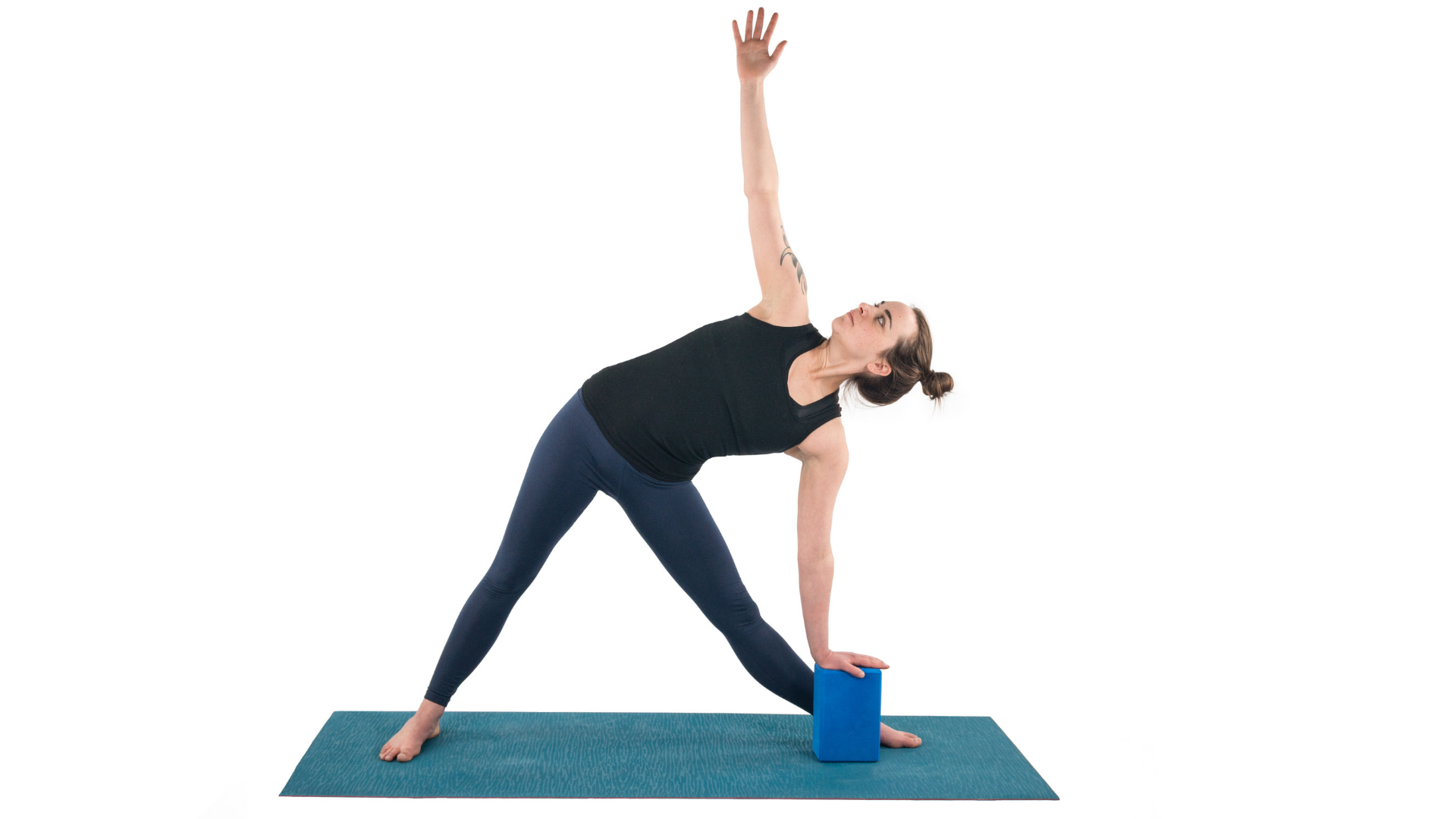 Woman practicing triangle pose with a block.