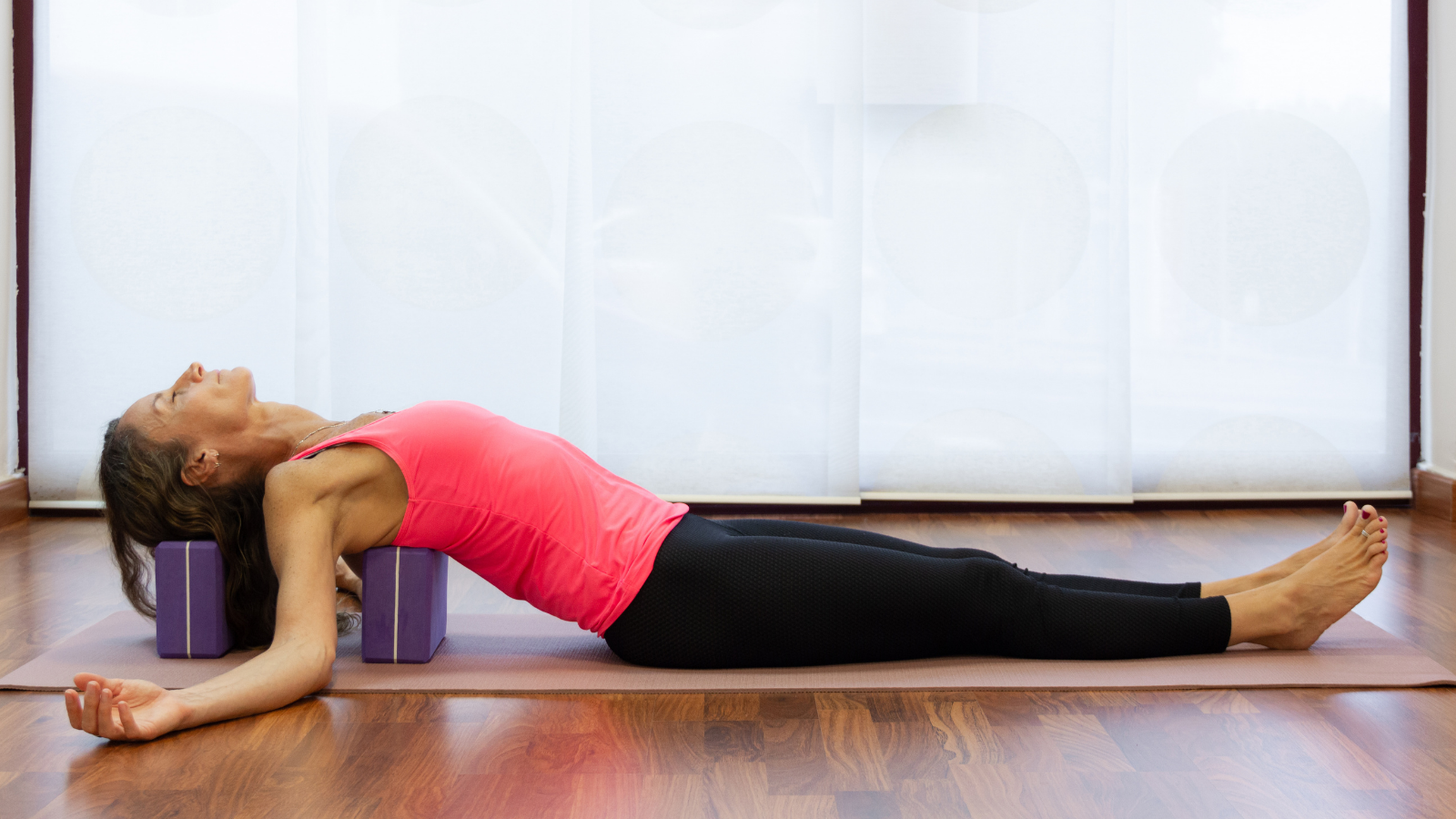 How to practice Supported Fish yoga Pose (Salamba Matsyasana) variation to help reduce the symptoms of tension headaches