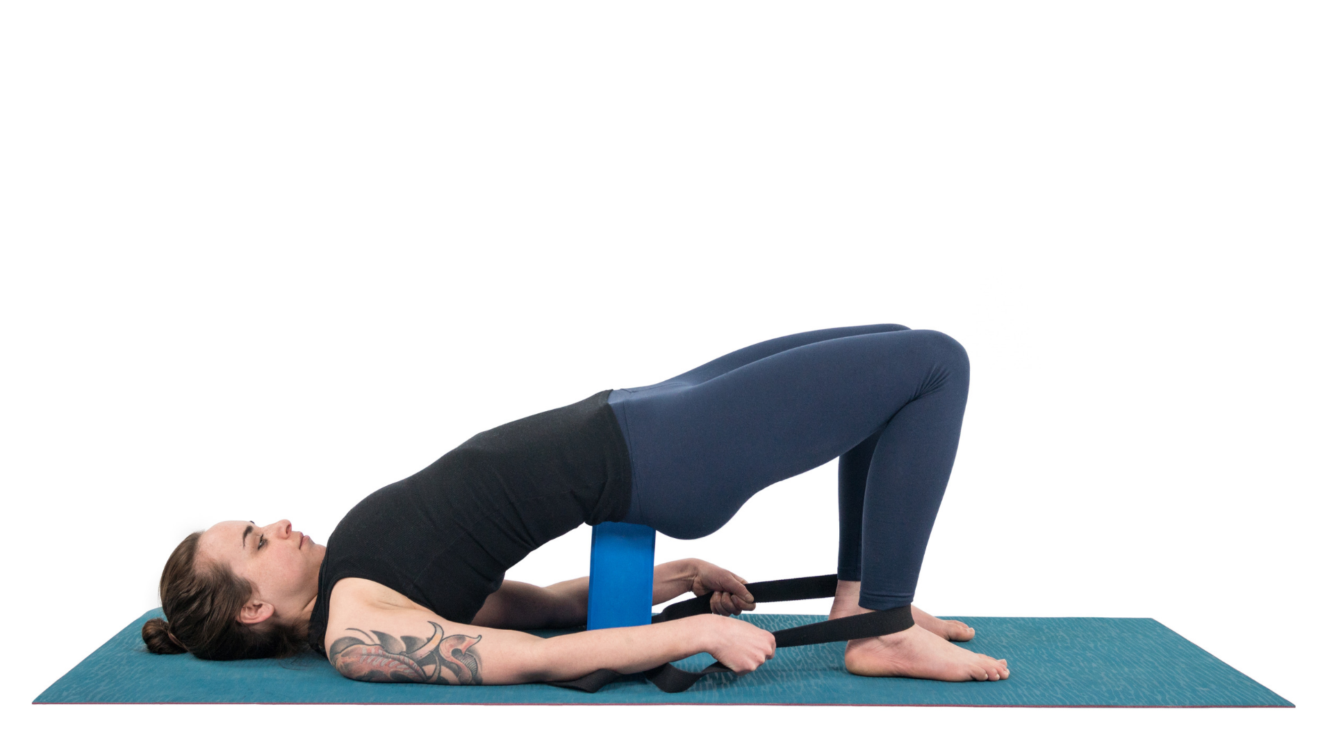 Woman practicing bridge pose with yoga block under her hips.