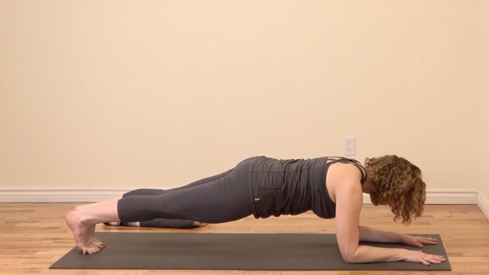 Practicing Forearm Plank or Ardha Phalakasana to strengthen arms, shoulders, and the core