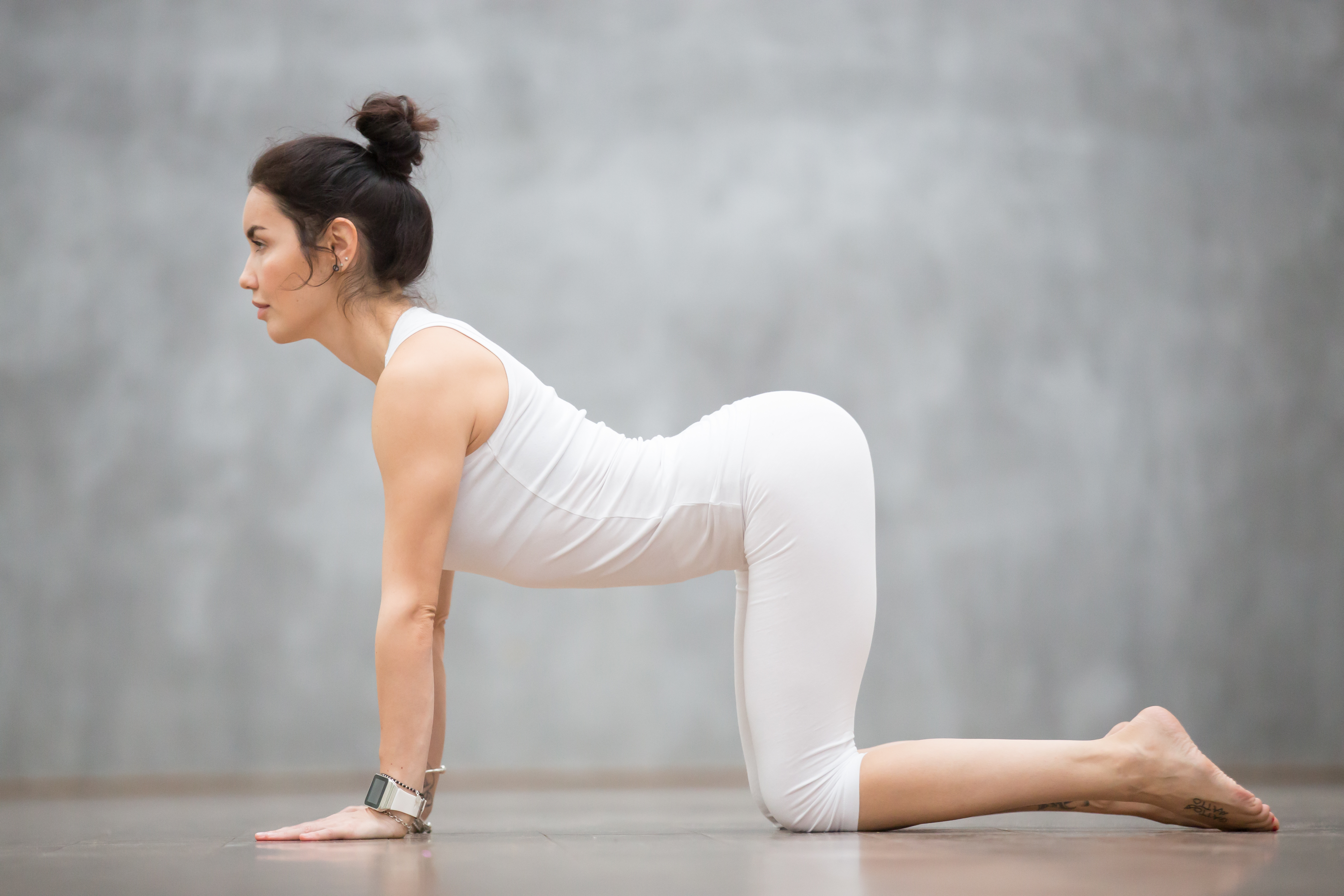 Woman practicing yoga at home cat cow pose