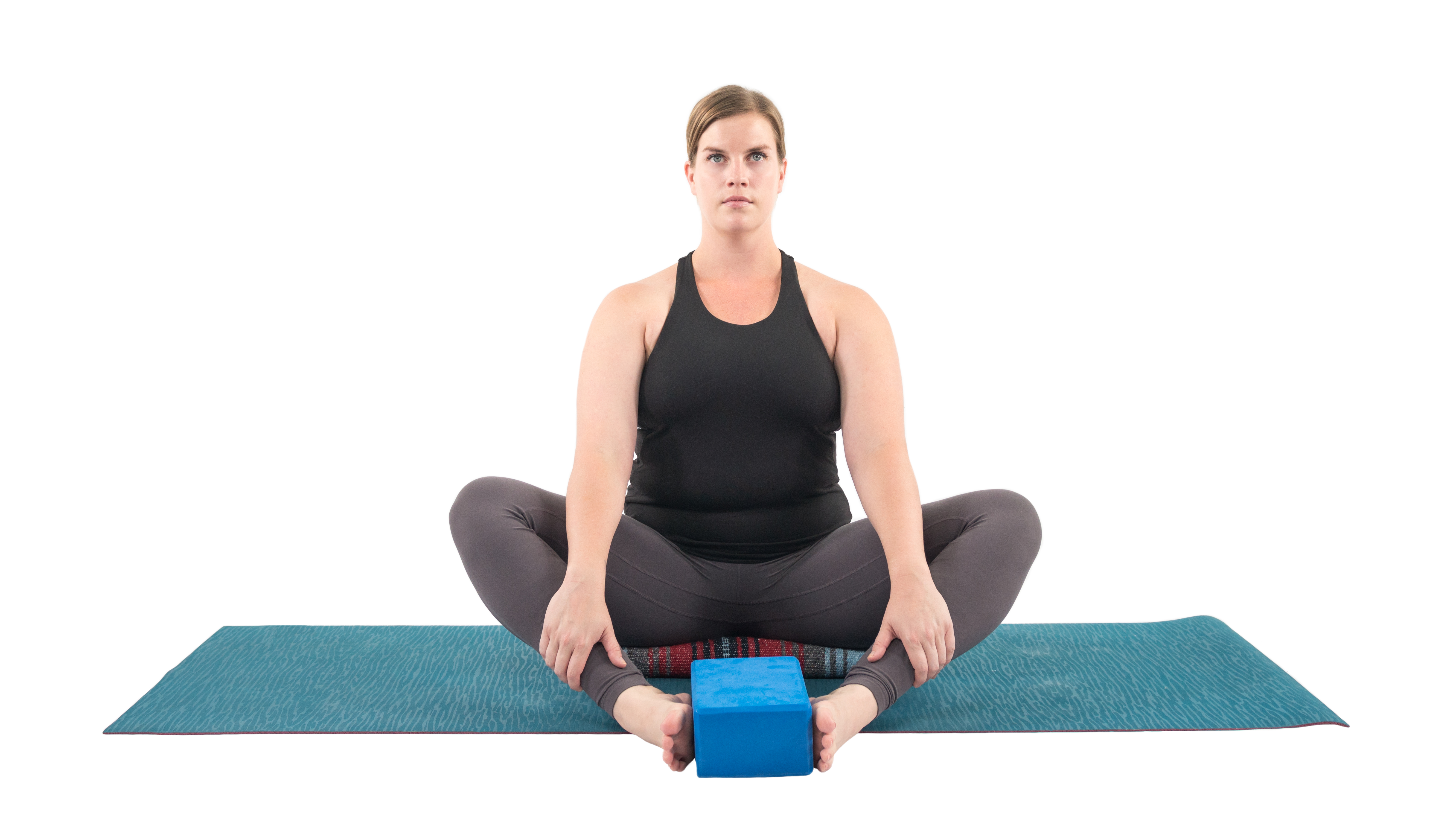 Woman in Bound Angle Pose (Baddha Konasana), a yoga pose to prepar the muscles of the hips for the proper practice of the Warrior 2 series.
