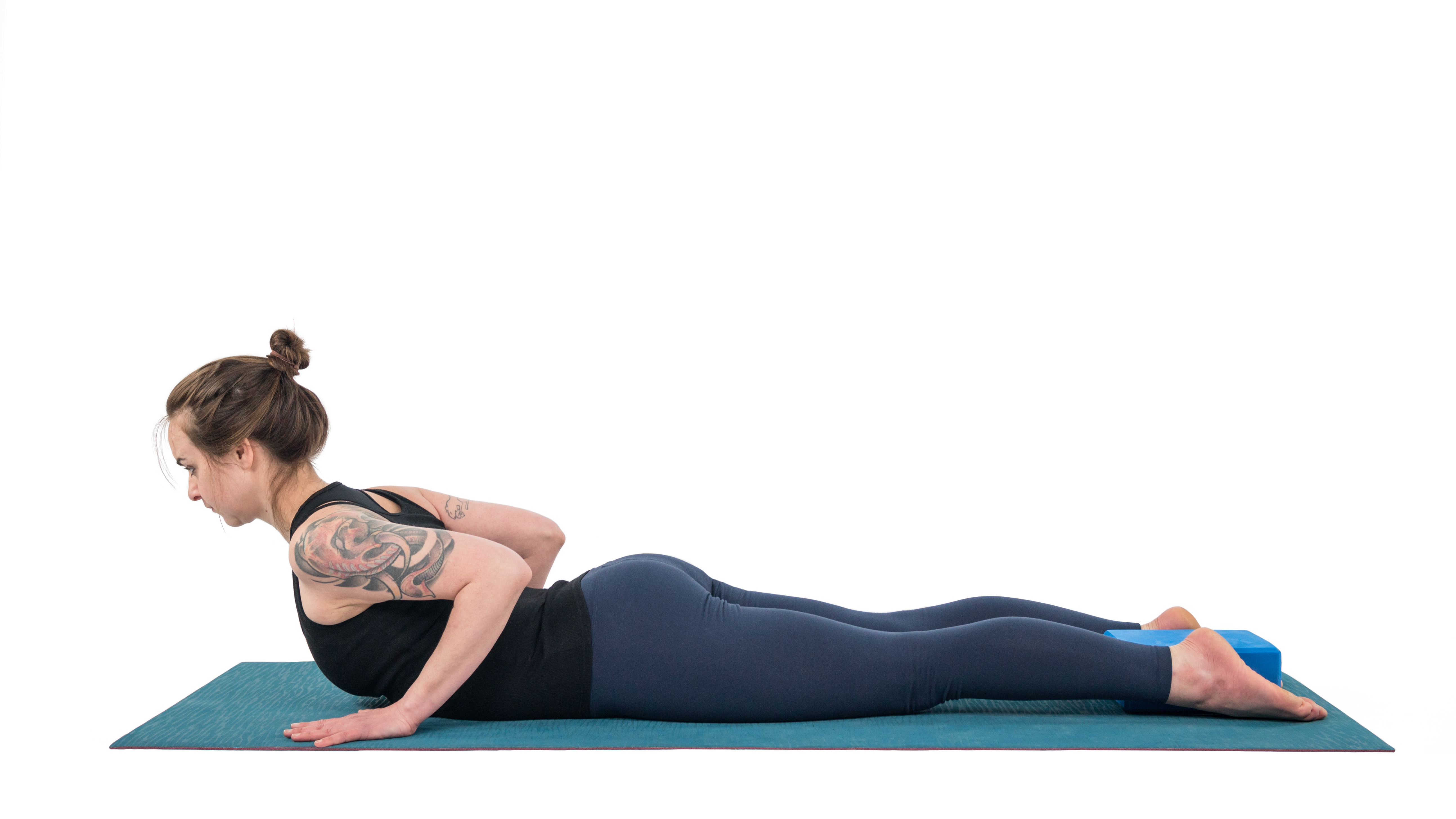 woman in cobra pose, Bhujangasana, with prop modification of block between ankles
