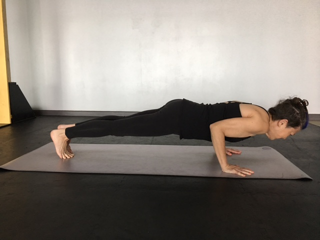 A woman practicing yoga for arm strength in Four-Limbed Staff Pose (Chaturanga Dandasana)