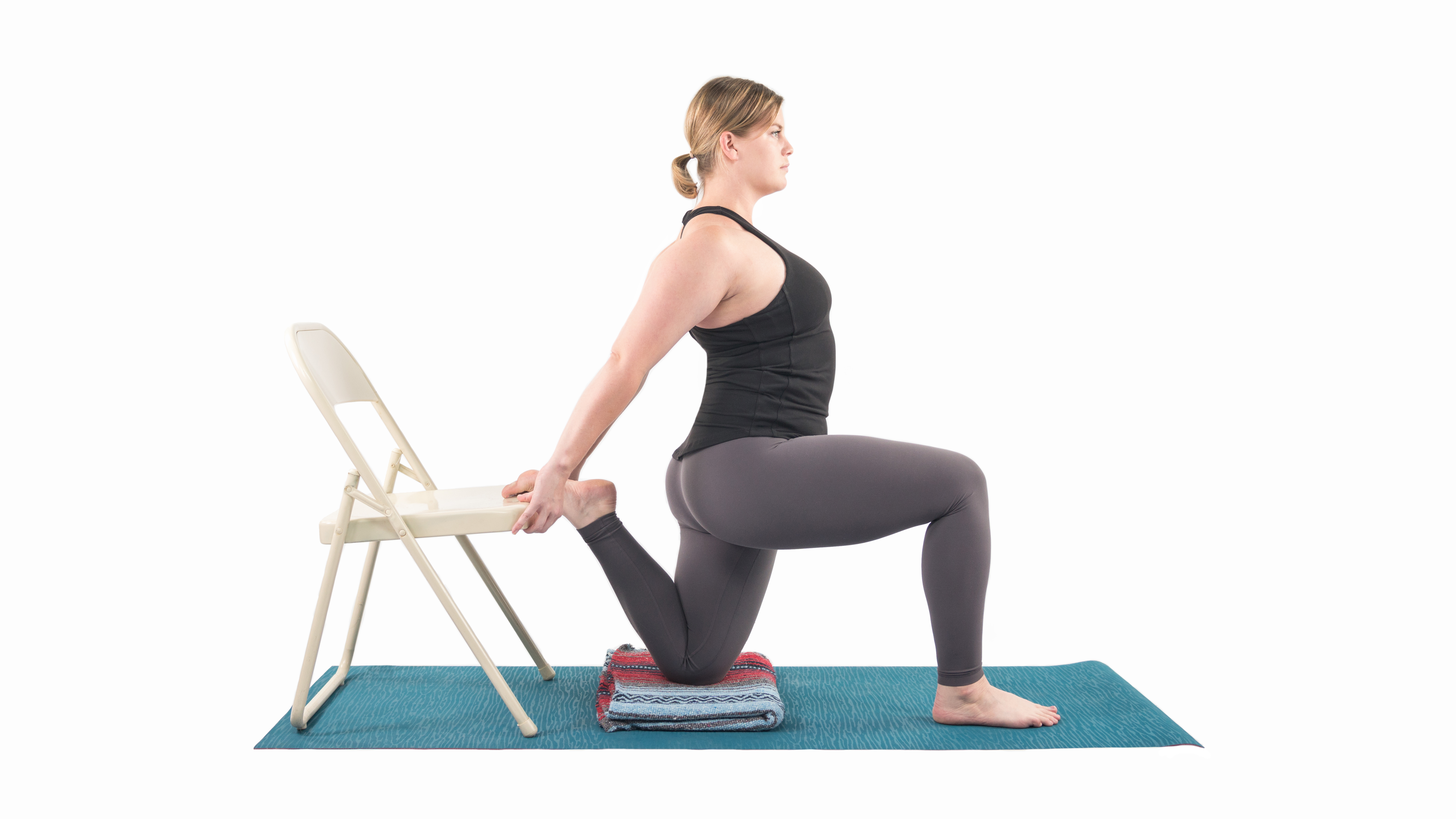 Woman performing a quad stretch with the support of a chair in preparation for the Dancer Pose