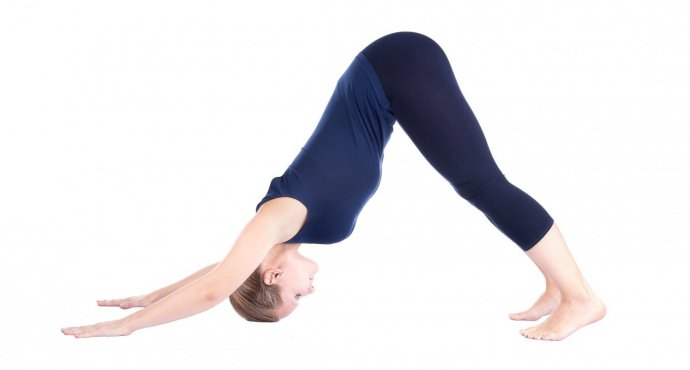 woman practicing downward-facing dog, adho mukha svanasana yoga pose to lengthen the spine