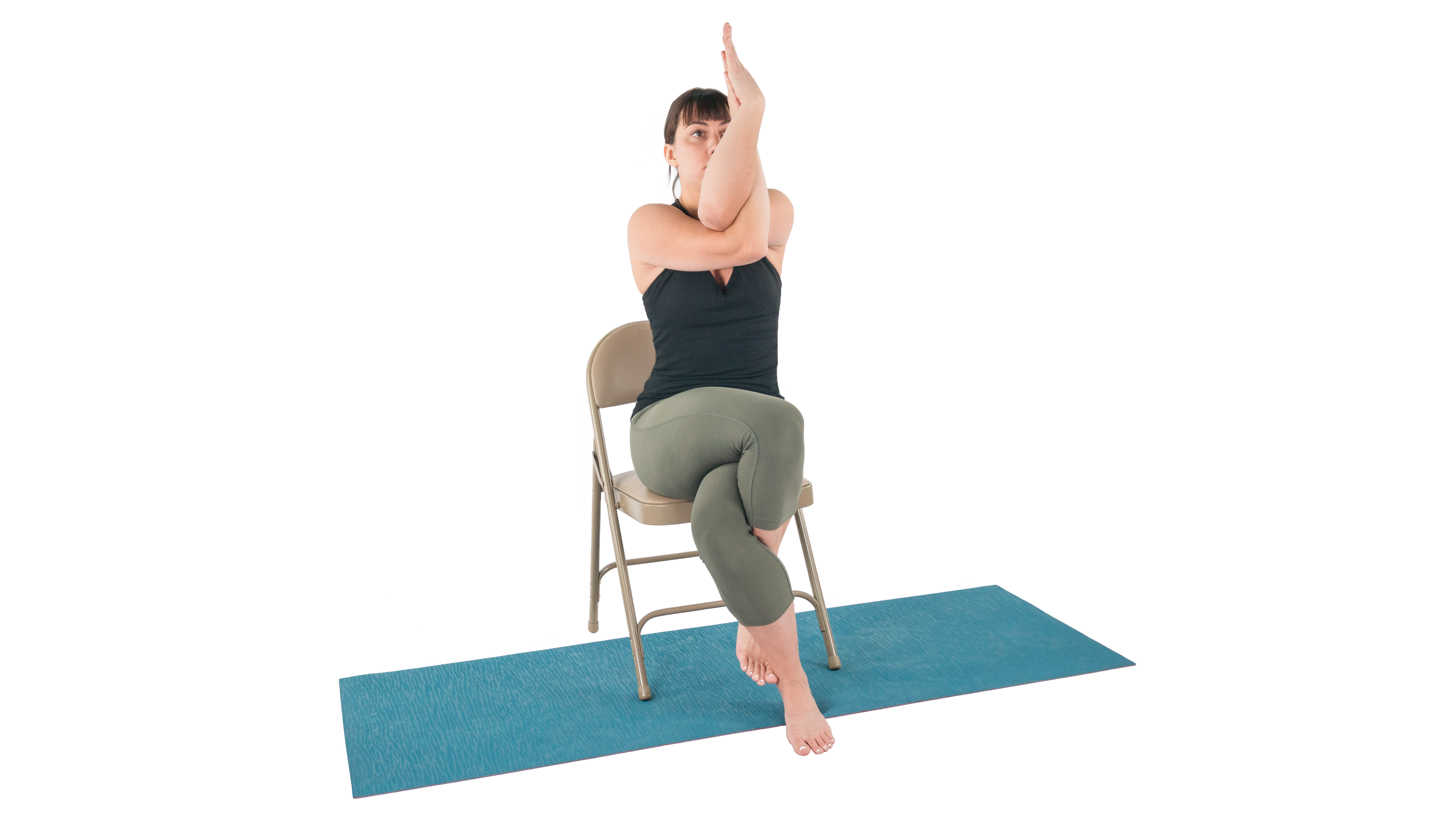 beginner yoga student enjoying the benefits of modified eagle pose in a chair in yoga class