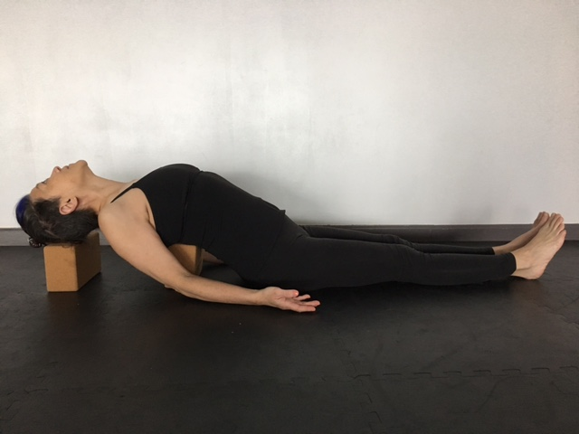 woman practicing yoga, doing Supported Fish Pose (matsyasana) with block support modification for neck and shoulder pain