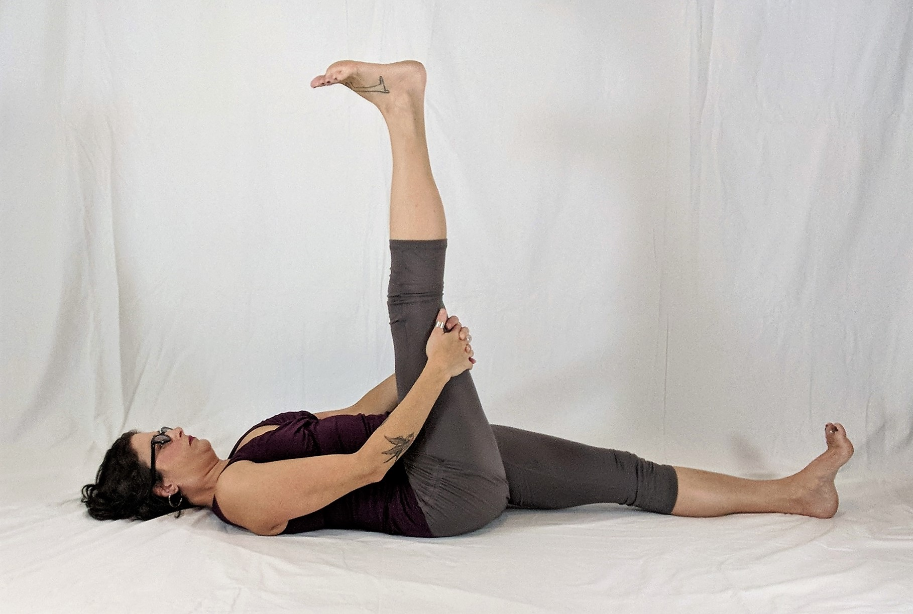 Reclining floor yoga pose with one leg raised
