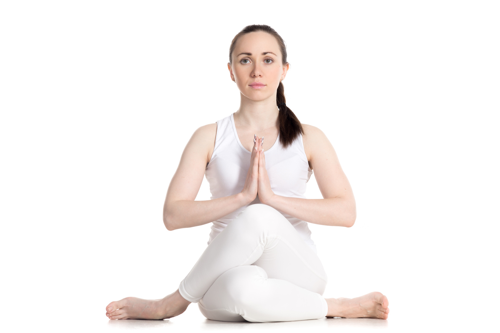 Woman practicing gomukhasana (cow face yoga pose) to stretch the gluteal muscles