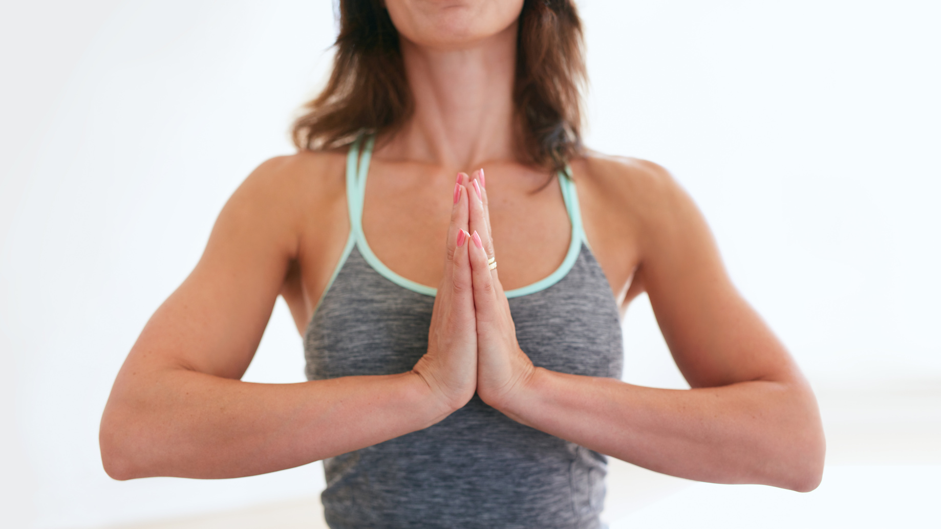 A woman in prayer position (Anjali Mudra) in order to stretch and strengthen weak wrists in preparation for yoga