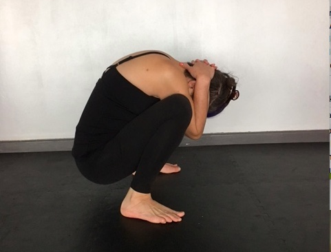 Woman practicing yoga for neck and shoulder pain, in Garland Pose (Malasana), with hands pulling on neck