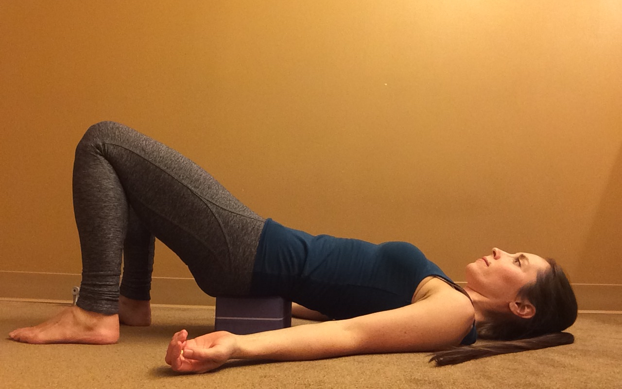 A woman in Supported Bridge (Salamba Setu Bandha Sarvangasana), a yoga pose to massage the psoas muscle
