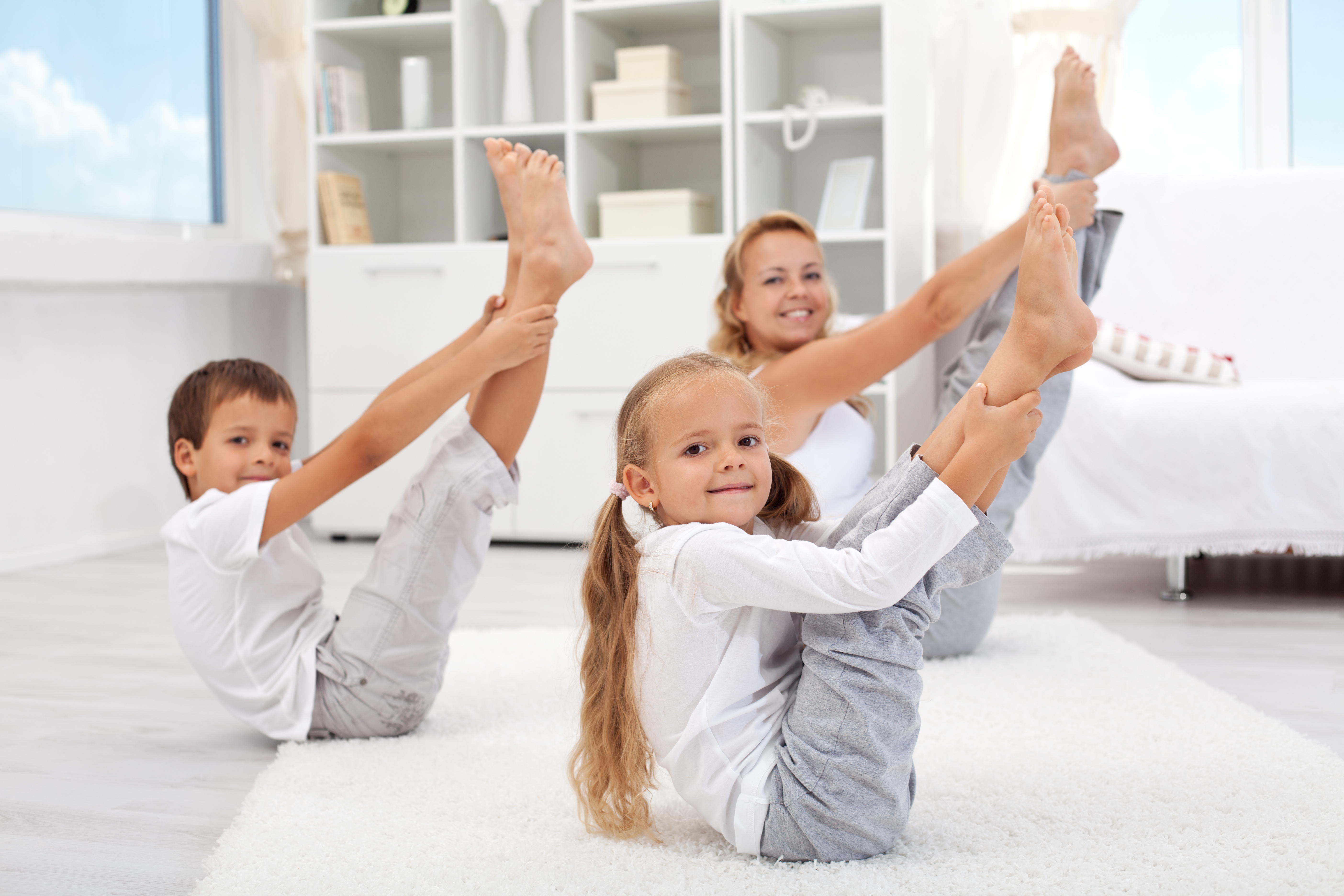 Mother and children practicing yoga together in Boat Pose (Navasana)