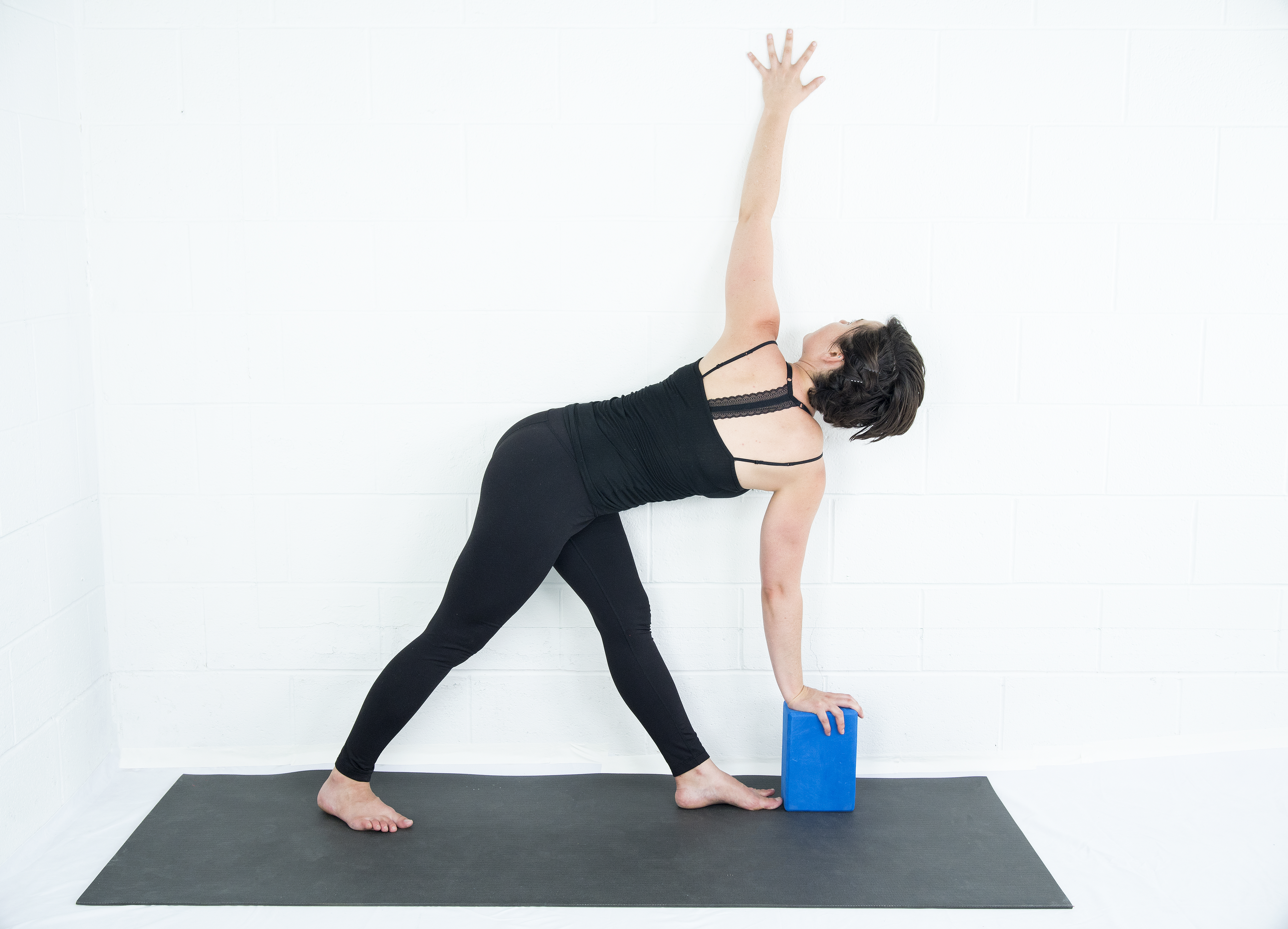 woman in Parvrtta Trikonasana, Revolved Triangle Pose with block and wall prop variation