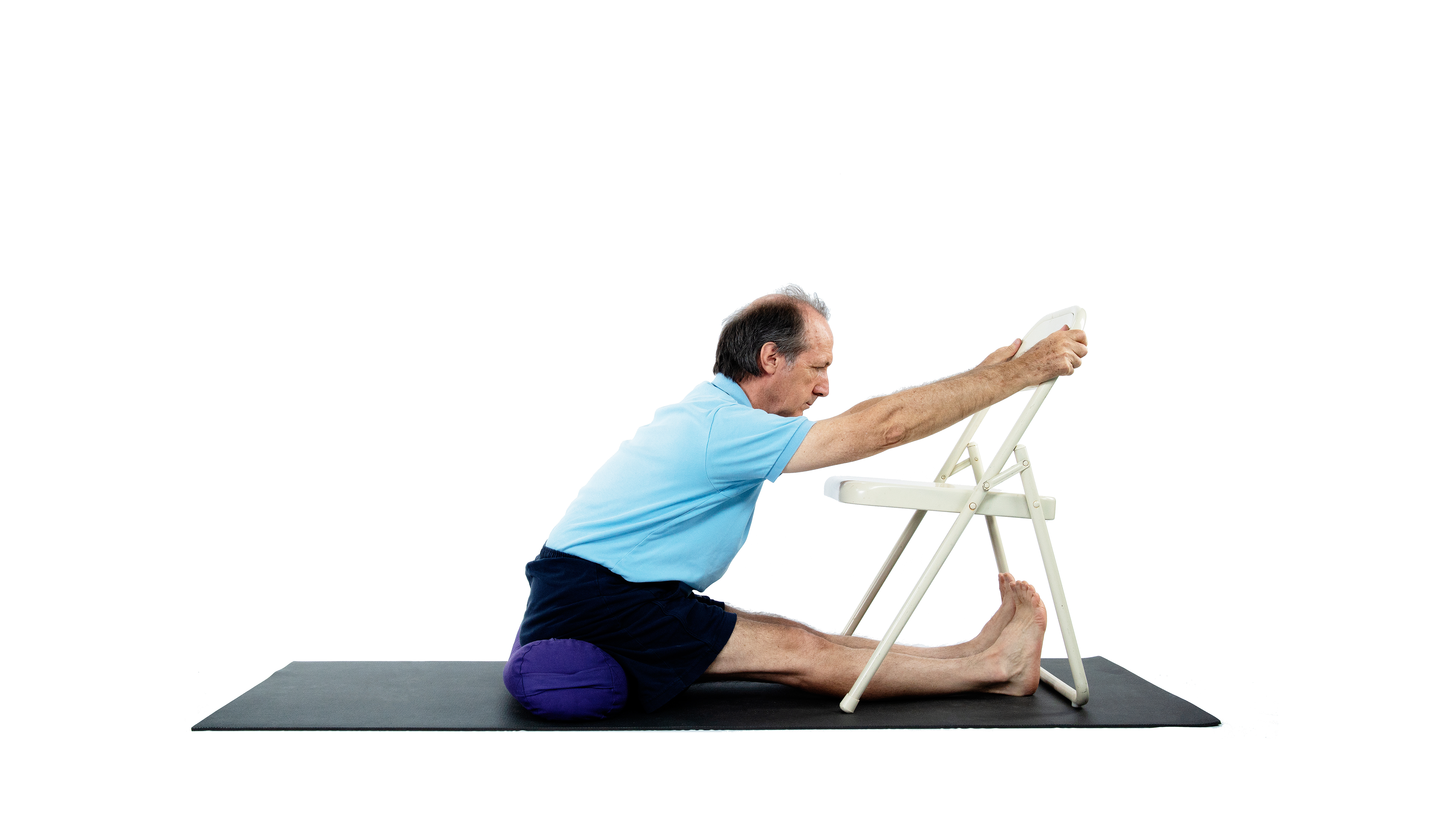 Seated Forward Fold Paschimottanasana with chair and bolster used as props for this variation