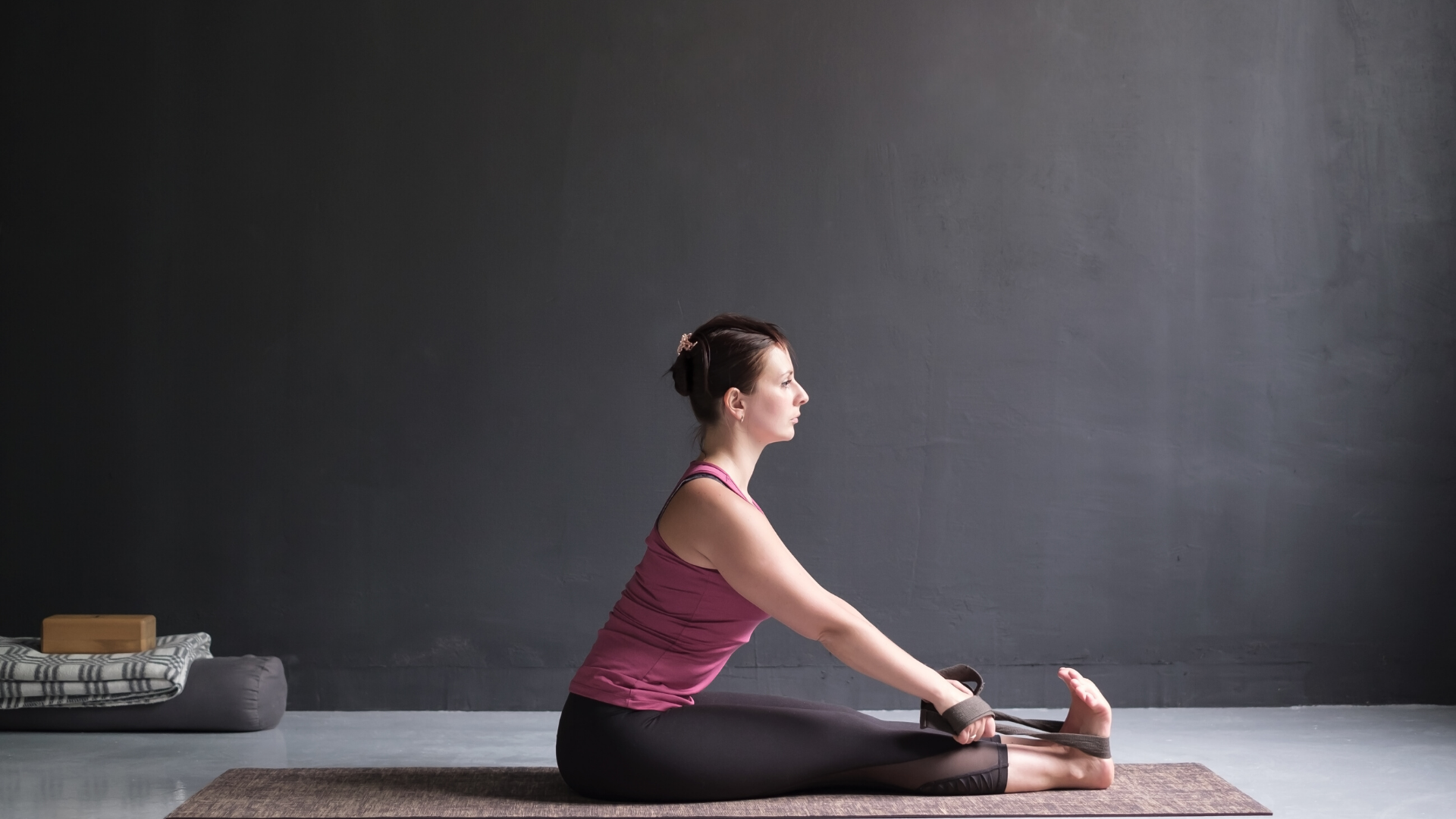 Woman practicing yoga seated forward bend with yoga strap.