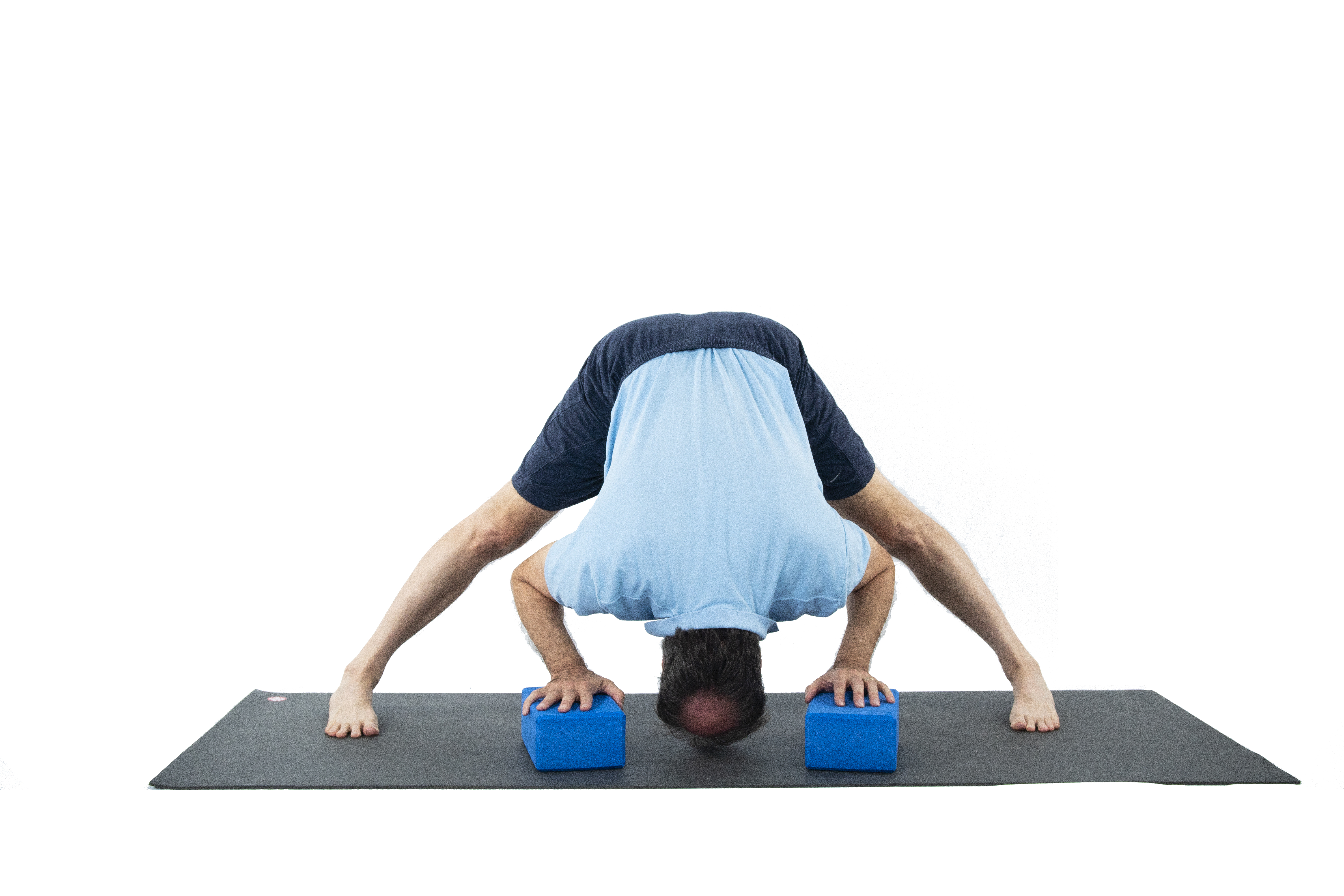 A man doing Wide-Legged Forward Fold (Prasarita Padottanasana) to prepare for the Warrior 2 yoga pose series