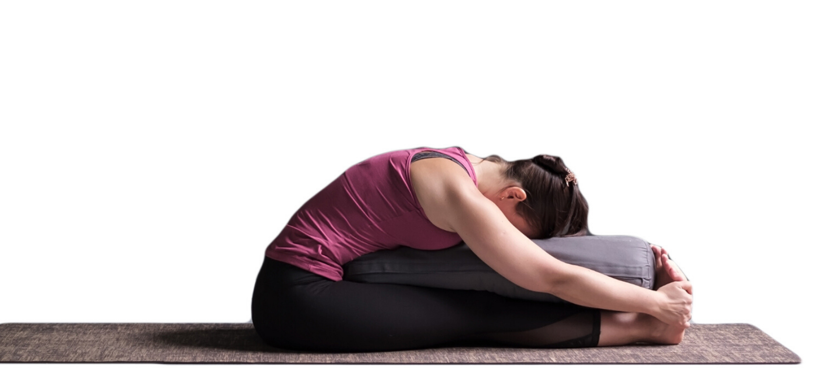 Female yoga student practicing seated forward bend (paschimottanasana)