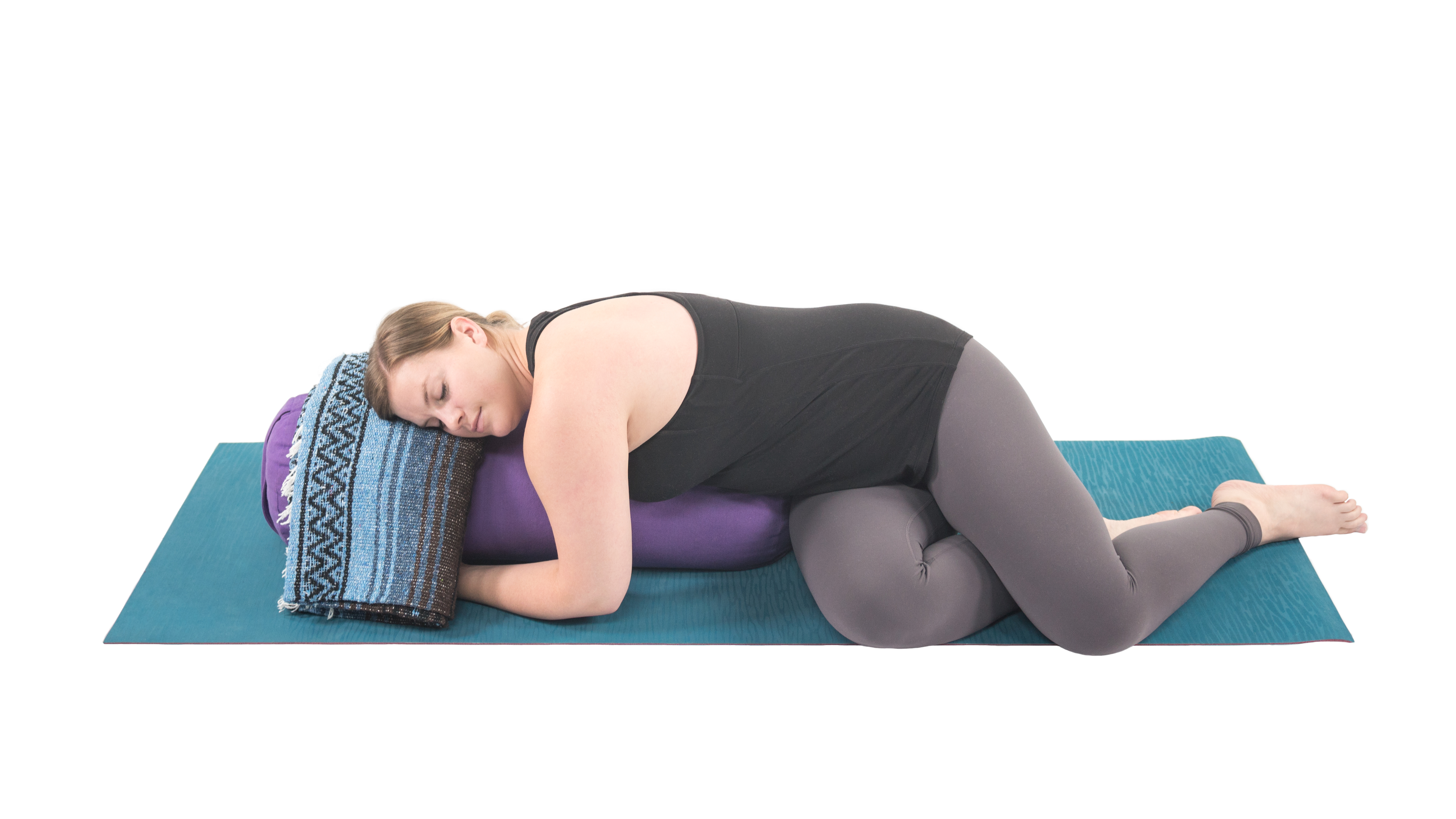restorative yoga, woman in supported prone twist with blanket and bolster props