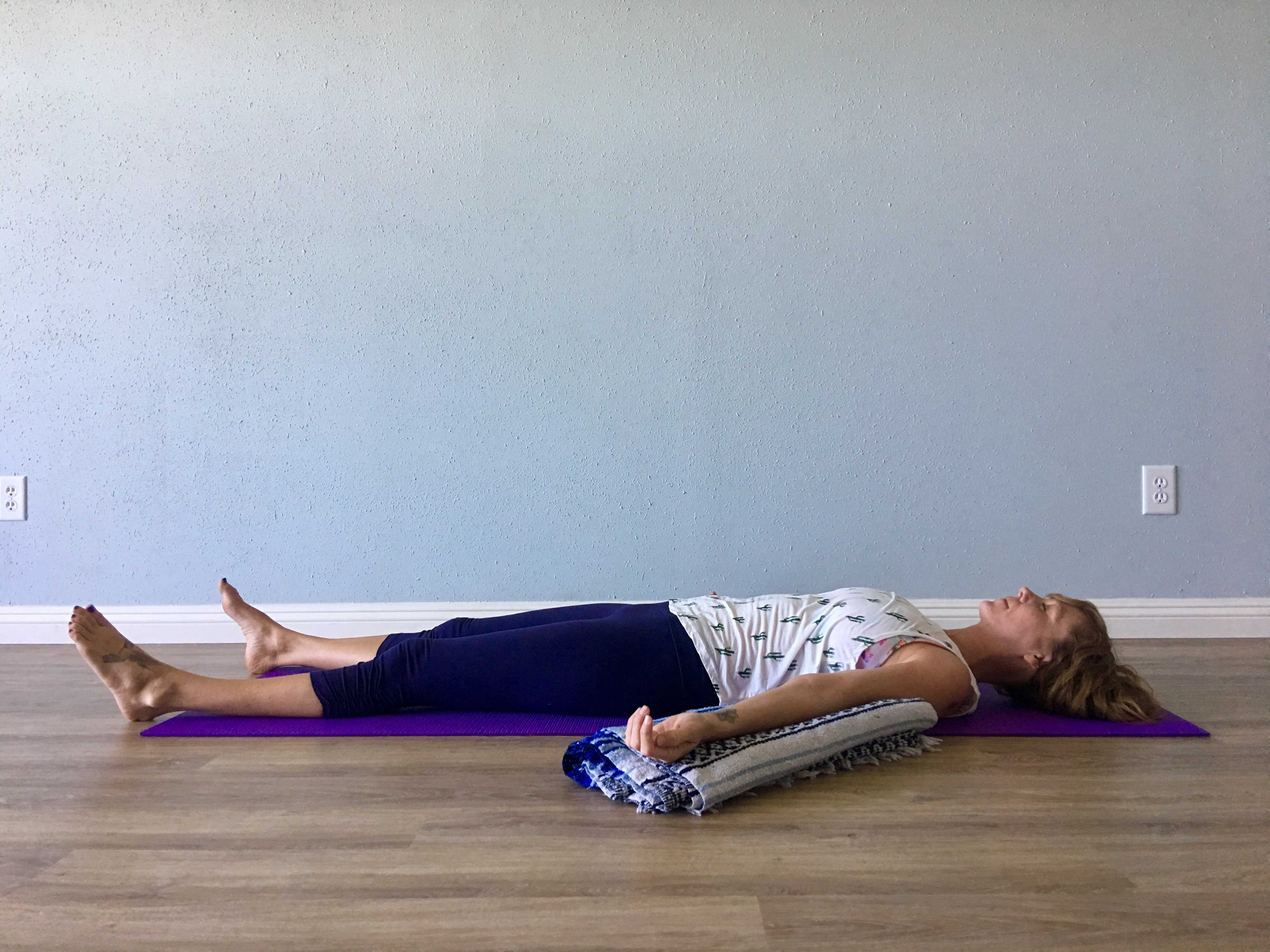 woman practicing yoga in modified savasana (corpse pose) with blanket support under arms