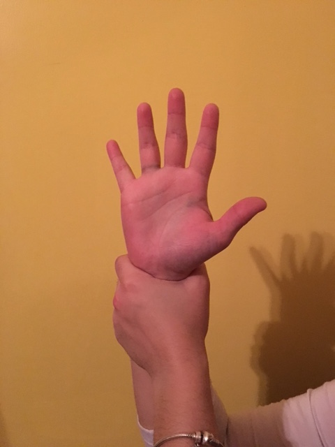 Holding wrist with other hand to gently pull down and stretch the wrist after arm strengthening yoga poses