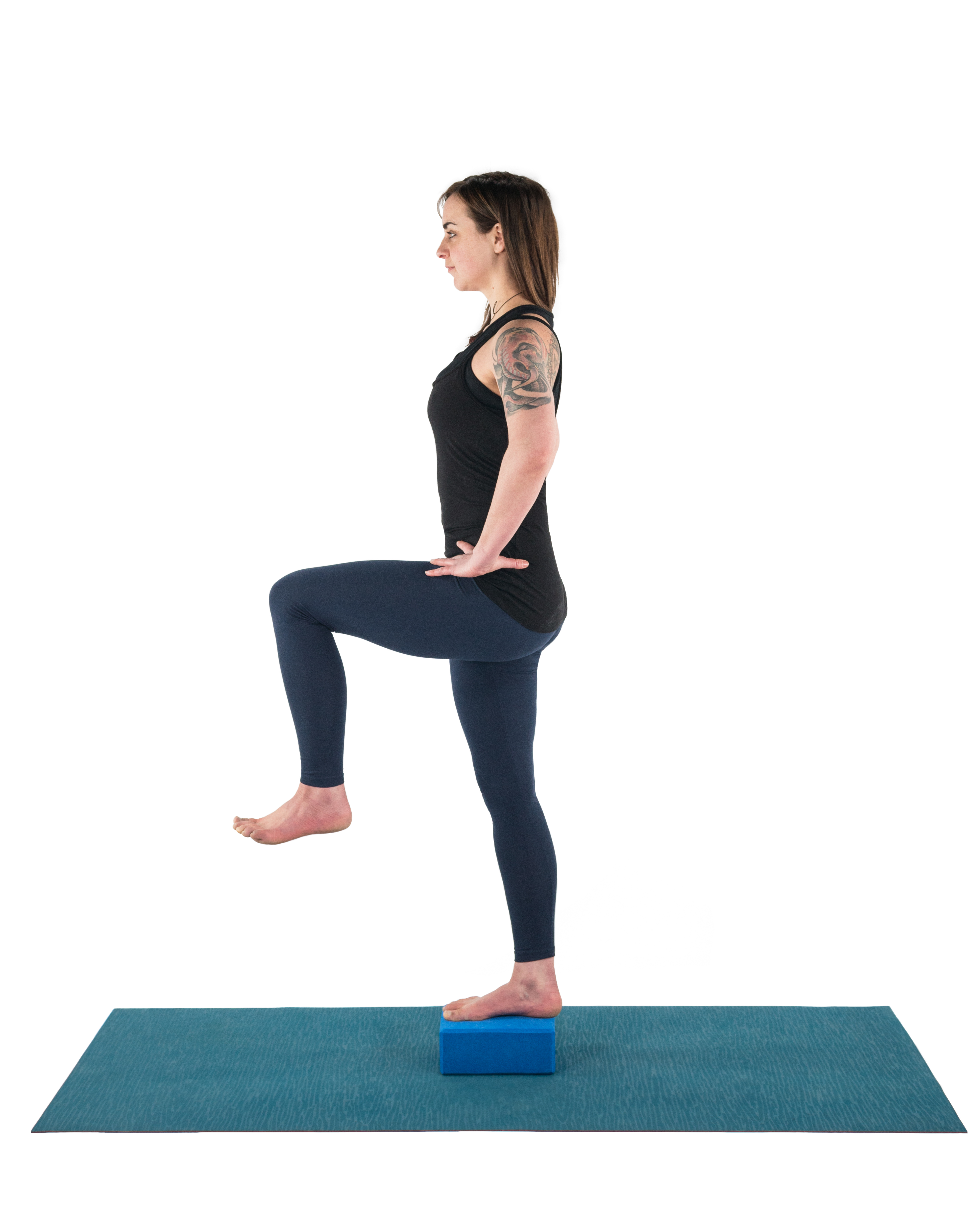 A woman in a balance yoga pose, standing with one foot on a block, to practice foot care and balance.