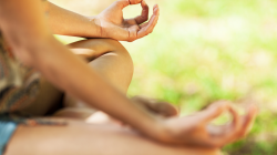 Woman sitting in Simple Easy Pose with her hands forming a mudra