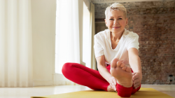Mature woman sitting on floor with one leg straight reaching forward by bending trying to touch toes