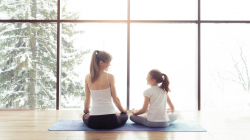 Woman and daughter meditating in front of winter window.