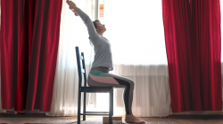yoga instructor demonstrating chair yoga pose for back health