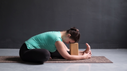 woman practicing janu sirsasana yoga pose with block under her forehead