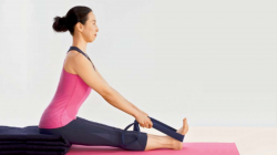 student enjoys benefits of Seated Forward Bend Pose (Paschimottanasana) variation