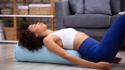 woman practicing restorative yoga, reclined modification with bolster