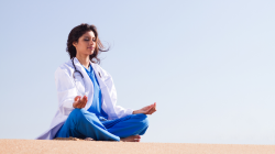 Female medical professional practicing yoga meditation outside.