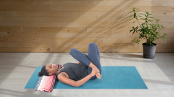 yoga woman practicing reclined cow face pose, gomukhasana