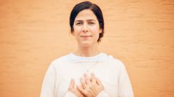 yoga woman standing calm with hands over heart in self-acceptance