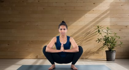 yoga instructor demonstrating tips for practicing malasana in yoga class