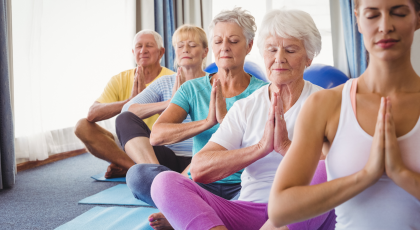 Group of older yoga students practicing to help the symptoms of rheumatoid arthritis