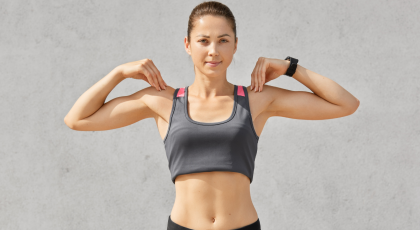 Waist up shot of woman keeps both hands on shoulders, does exercises during morning workout