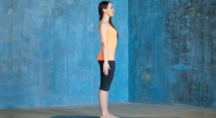 Side view portrait of a young woman practicing Tadasana or Mountain Pose indoors