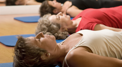Yoga class practicing in rest mode recognizing the importance of sleep