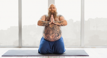 Tattooed man practicing yoga.
