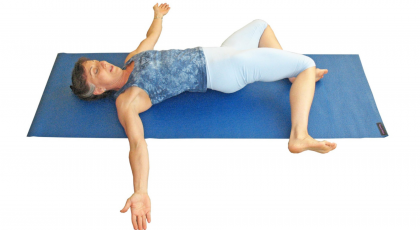 woman practicing supine twist with therapeutic yoga for back pain