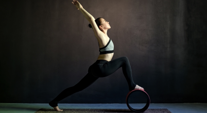 woman practicing yoga warrior 1 with yoga wheel