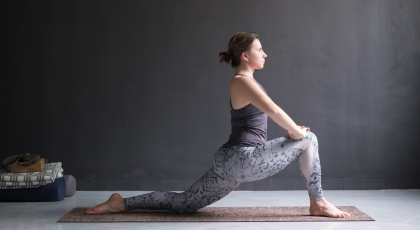 Woman practicing yoga Anjaneyasana or low crescent lunge pose
