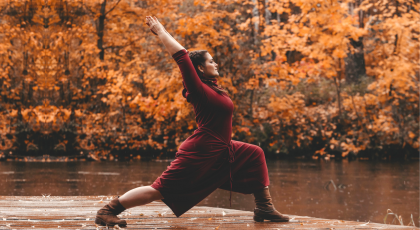 curvy woman practicing warrior 1 on dock near lake and autumn fall leaves