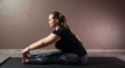 Woman practicing yoga Seated Forward Bend Pose (Paschimottanasana)
