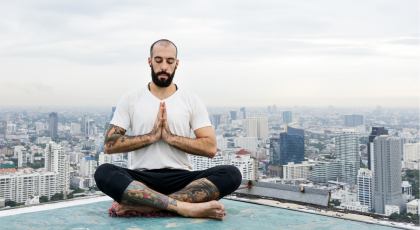Man practicing yogic meditation on rooftop and contemplating, Svadhyaya, equality and human rights